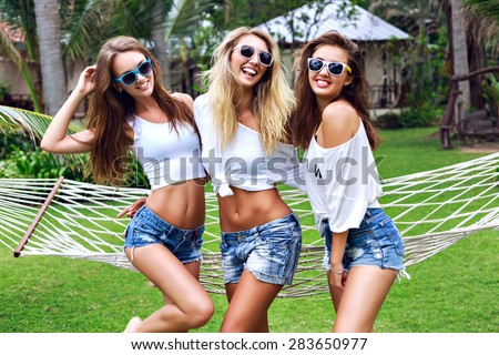 Summer lifestyle portrait of thee hipster stylish women with fit sexy body, wearing denim mini shorts and vintage sunglasses. Girls friends going crazy, having fun, dancing, laughing and screaming. - stock photo
