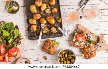 Summer lunch served on a wooden picnic table with fruits, various cheese, vegetables, leaves of salad, olives, fruits juice  and oven sheet with cooked potatoes from above. Rustic mediterranean food. - stock photo