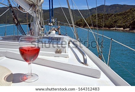 Summer Luxury - a glass of Rose on the deck of a yacht in the Marlborough Sounds, New Zealand. - stock photo