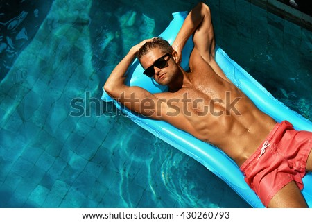 Summer Man Body Sun Skin Care. Beautiful Model With Sexy Body In Swimwear Tanning, Floating On Mattress In Swimming Pool Water. Fitness Male With Healthy Tan Relaxing At Relax Spa Resort. Summertime - stock photo