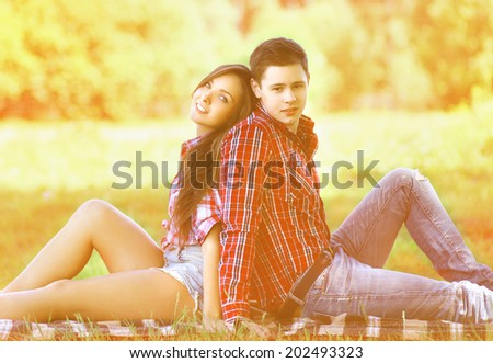 Summer modern pretty couple resting on the grass in the city park - stock photo