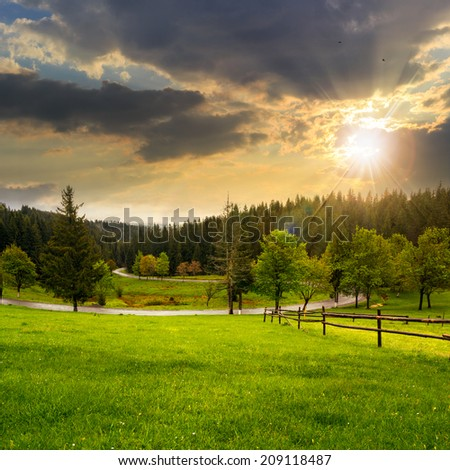 summer mountain landscape. curve asphalt road and wooden fence near the meadow on hillside with forest at sunset - stock photo