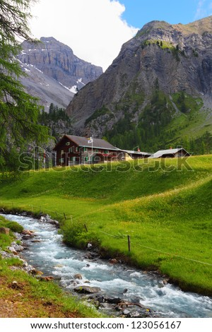 Summer mountain landscape with chalet and green meadow with stream in the foreground, Sertig Dorfli, Davos, Switzerland - stock photo
