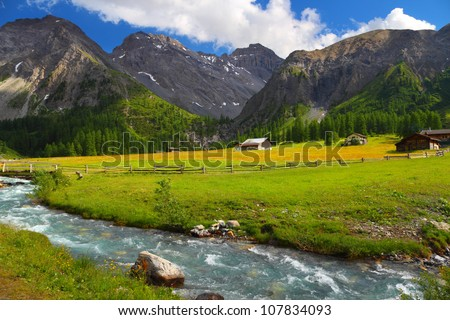 Summer mountain landscape with chalet on a meadow and stream in foreground, Sertig Dorfli, Davos, Switzerland - stock photo