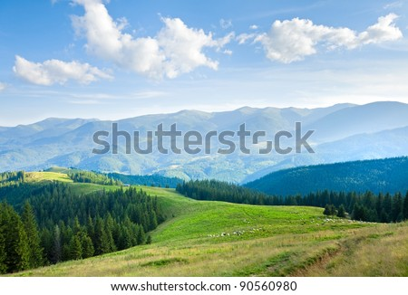 Summer mountain plateau landscape with dirty road on hill top - stock photo