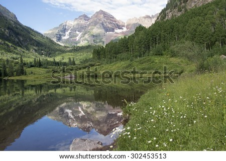 Summer mountain scenic - Colorado's Maroon Bells reflected in Maroon Lake with wildflowers in foreground, near Aspen - stock photo