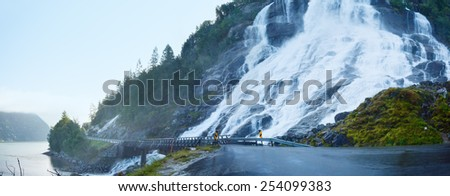 Summer mountain waterfall on slope near road along the Sandvinvatnet lake (Norway). - stock photo