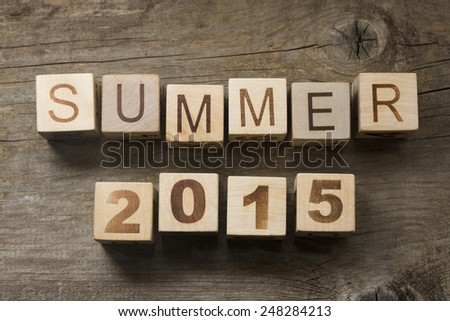 Summer 2015 on wooden blocks on a wooden background - stock photo