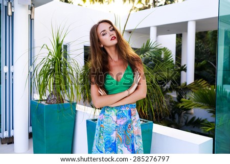 Summer outdoor fashion portrait of stunning brunette woman with long hairs and bright make up, wearing sexy silk dress, posing at luxury villa, evening sunlight. - stock photo