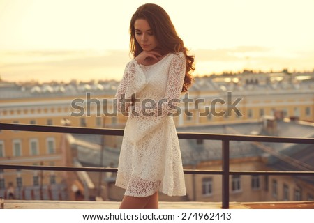 Summer outdoor porttrait of young pretty elegant girl posing at roof at sunset. Lovely soft back light. View on city buildings and roofs. - stock photo