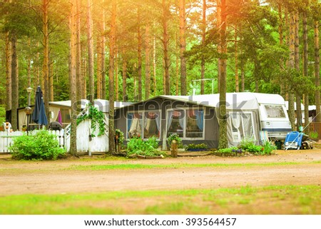 Summer outdoor recreation, Scandinavian vacation. Camping vans and tents parked in a wooded campsite among pine trees. Finnish Gulf. Area for camp in woods. Hamina, Finland, Suomi - stock photo