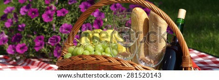 Summer picnic basket with fruits, glasses and bottle of wine - stock photo