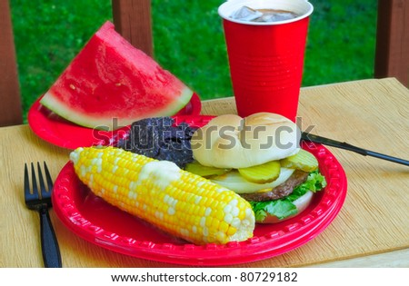 Summer picnic fare - hamburger, sweetcorn, chips, and watermelon - in an outdoor setting - stock photo