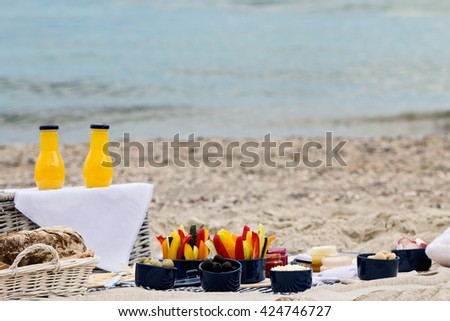 Summer picnic on the beach. Serving picnic utensils blue with vegetables and sauces on striped tablecloths and knitted pillow. Selective focus. - stock photo