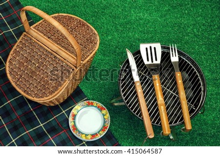 Summer Picnic Scene On The Grass. Portable Barbecue Grill With Charcoal Briquettes, BBQ Tools Kit, Closed Wicker Basket And Blanket. Top View - stock photo