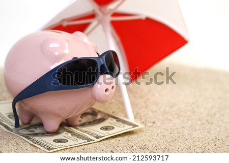 Summer piggy bank standing on towel from greenback hundred dollars with sunglasses on the beach sand under red and white sunshade  - stock photo