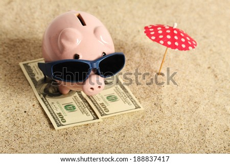 Summer piggy bank standing on towel from greenback hundred dollars with sunglasses on the beach and red parasol - stock photo