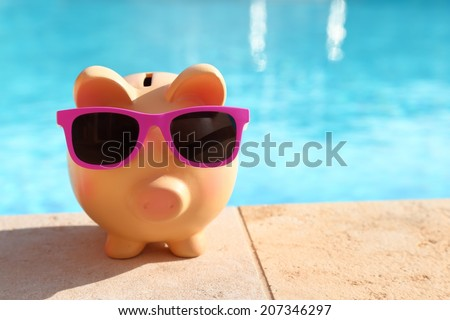 Summer piggy bank with sunglasses in front of a swimming pool - stock photo