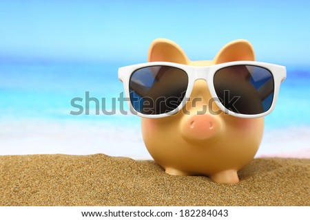 Summer piggy bank with sunglasses on the beach - stock photo