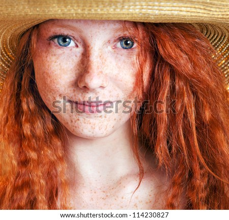 Summer portrait, beautiful freckled young woman wearing straw hat - stock photo