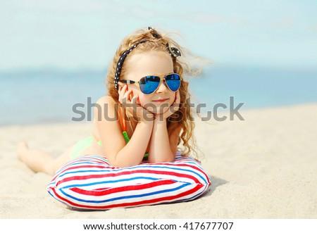 Summer portrait child lying resting on beach over sea - stock photo