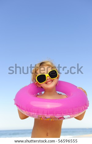 summer portrait: child with sunglasses and inflatable ring at the beach - stock photo