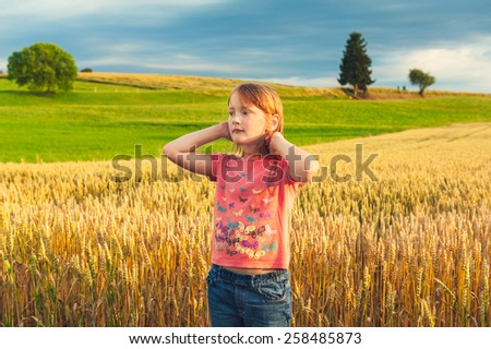 Summer portrait of a cute little girl of 7 years old, playing in wheat field on sunset - stock photo