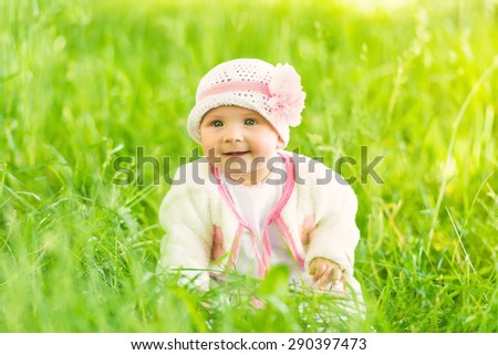 Summer portrait of beautiful baby girl sitting in grass - stock photo