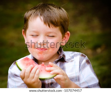Summer portrait of cute young child eating watermelon outdoors - stock photo