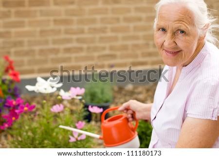 Summer portrait of elderly woman watering her flowers - stock photo