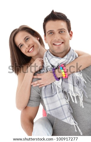 Summer portrait of happy couple, handsome man carrying pretty girlfriend on back, laughing. - stock photo