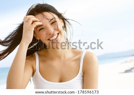 Summer portrait of happy young woman in the wind smiling. - stock photo