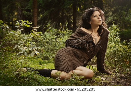 summer portrait of sexy girl sitting in a forest clearing among the green bushes and trees - stock photo