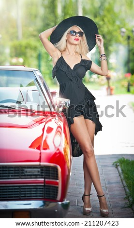 Summer portrait of stylish blonde vintage woman with long legs posing near red retro car. fashionable attractive fair hair female with black hat near a red vehicle. Sunny bright colors, outdoors shot. - stock photo