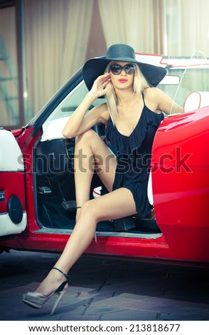 Summer portrait of stylish blonde vintage woman with long legs posing near red retro car. Fashionable attractive fair hair female near a red vintage vehicle. Sunny bright colors, outdoors shot. - stock photo