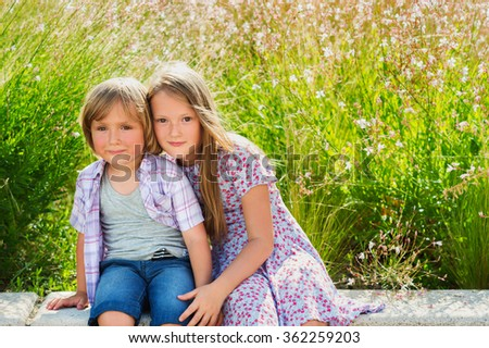 Summer portrait of two cute kids, young girl and her little brother - stock photo