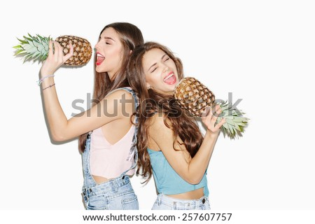 Summer portrait of two pretty brunette girl friends having fun with pineapple. Singing with closed eyes and smiling. Casual style, bright makeup, pink lips. White background, not isolated. Inside - stock photo