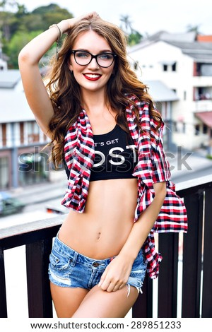 Summer portrait of young stylish hipster girl posing on balcony, wearing crop top, mini denim shorts, plaid shirt, clear glasses, sexy slim fit body, bright makeup, looking on camera. - stock photo
