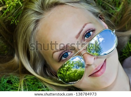 Summer reflection  in sunglasses of beautiful young woman on grass - stock photo