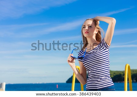 Summer relaxation concept.. Portrait girl with blue heart shaped sunglasses enjoying summer breeze outdoor on sky background - stock photo