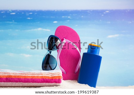Summer relaxation - sandy beach and sunbathing accessories - stock photo