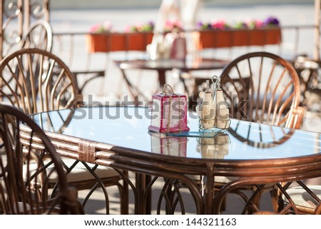 Summer restaurant cafe in Greece. patio with table and chairs near sea beach on Santorini island - stock photo
