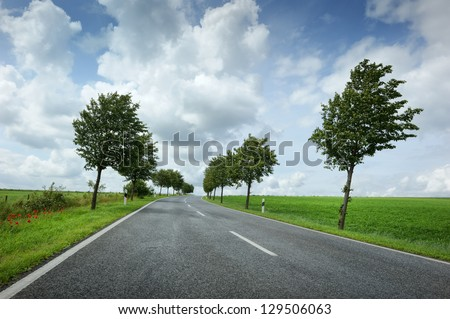 Summer road with cloudy and windy sky - stock photo