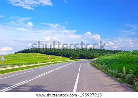 Summer road with road marking, meadow, forest and sky. - stock photo