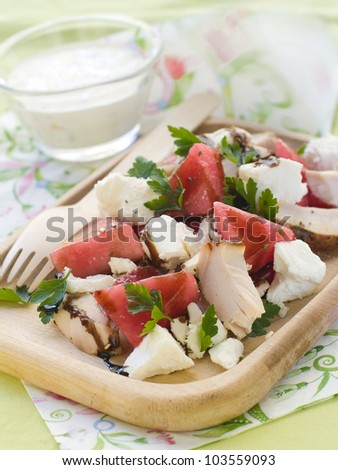 Summer salad from watermelon, chicken and feta on wooden plate, selective focus - stock photo
