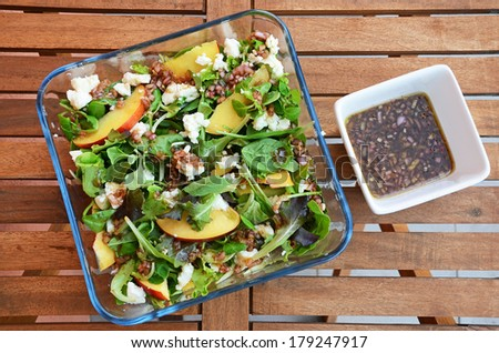 Summer salad - goat cheese, nectarine, spinach and shallot dressing - stock photo