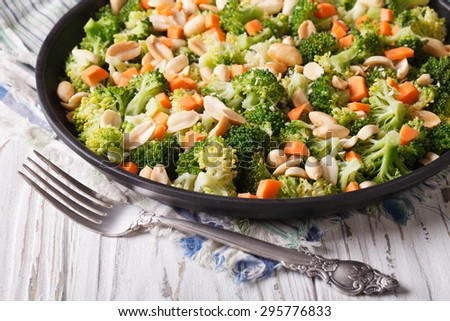 Summer salad with broccoli, carrots and peanuts close-up on a plate. horizontal  - stock photo