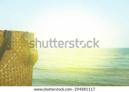 summer sale decorate with bamboo bag and eyeglass on wooden floor over blue sea background,vintage color filter. - stock photo