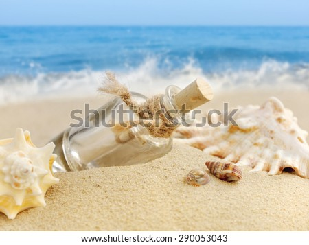 Summer sandy beach concept with letter in bottle - stock photo