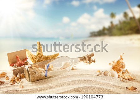 Summer sandy beach concept with letter in bottle, starfish and shells. - stock photo